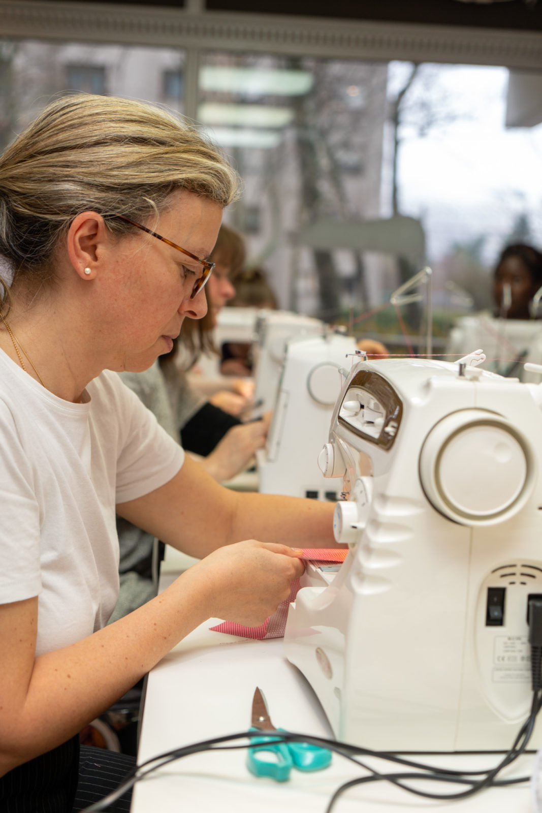 une élève entrain de coudre avec une machine à coudre dans l'atelier du Luxembourg