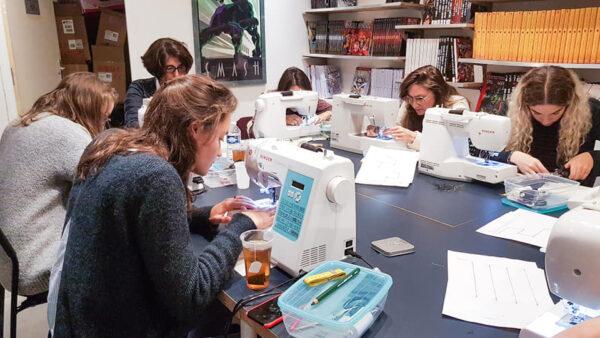des élèves autour d'une table dans les ateliers de cours de couture Paris