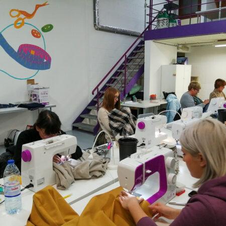 des élèves dans l'atelier de Charleroi avec les machines à coudre Cécile