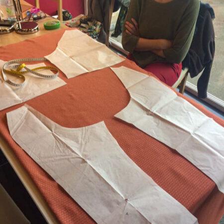 une élève de Liège plaçant les patrons sur le tissus