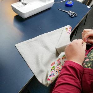 une personne cousant a main nue un tissu de Cours de couture à Paris