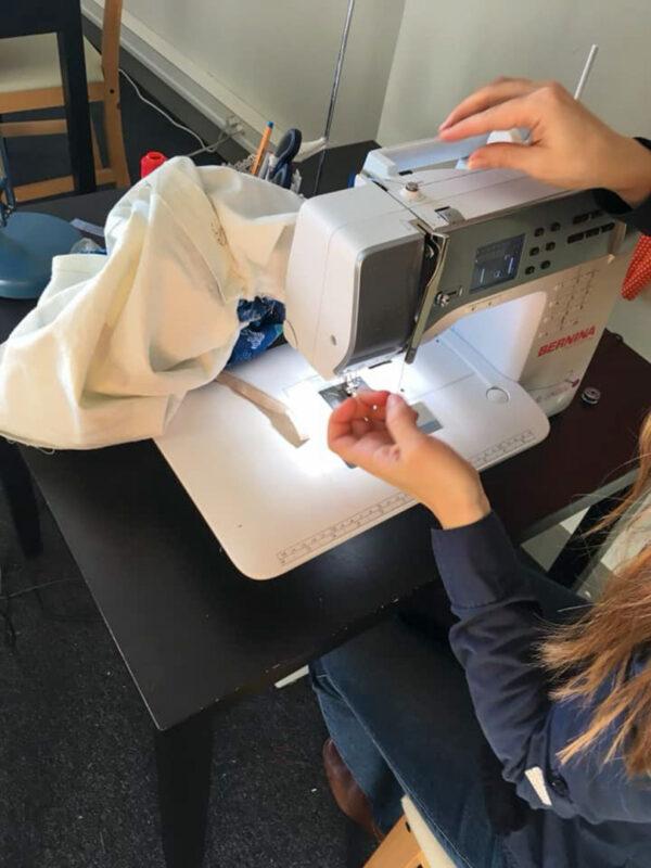 une apprenti cousant sur une machine a coudre bermina cours de couture à Woluwe