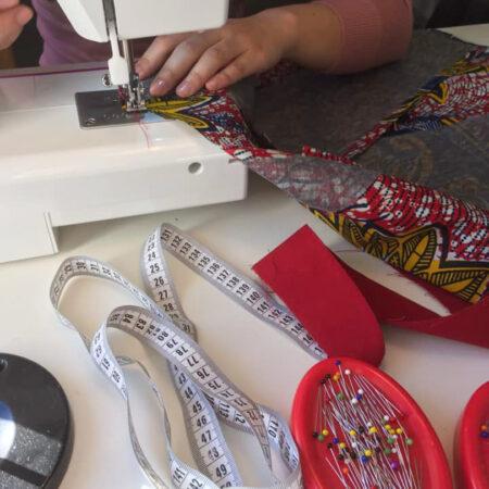 Une apprenti cousant un long tissu a l'atelier de Cours de couture à Lasne