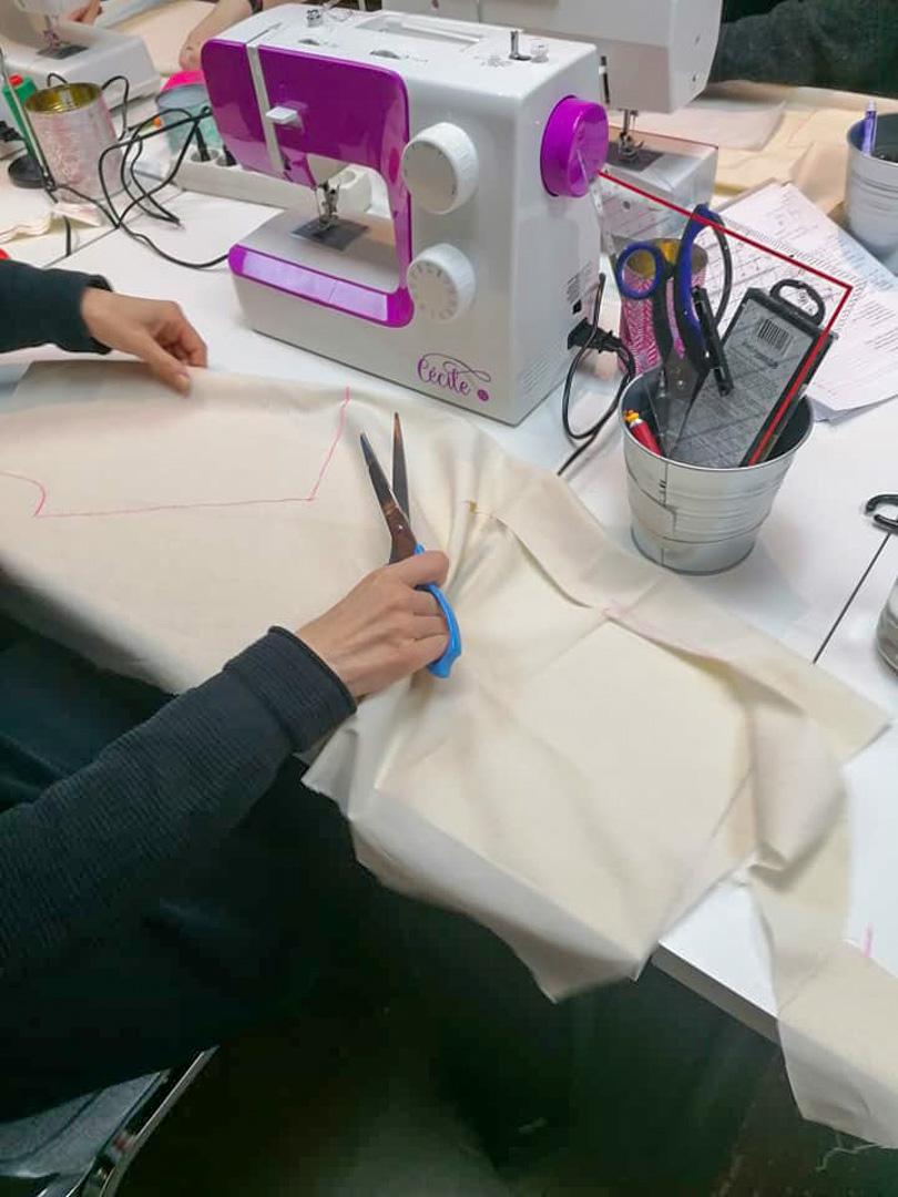 Découpage de tissu par une élève du Luxembourg à côté de la machine à coudre Cécile