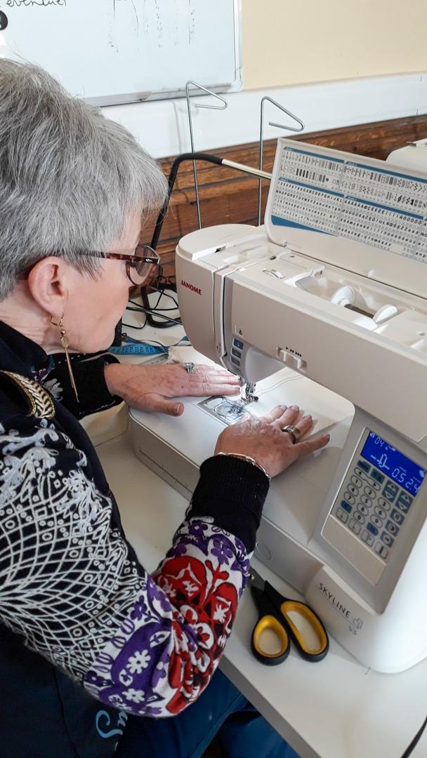 une personne cousant sur un matériel de couture singer cours couture à Namur