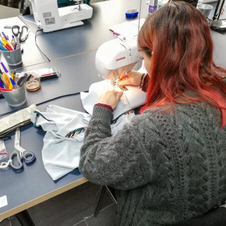 Une élève en plein couture de son haut dans notre atelier à Mons