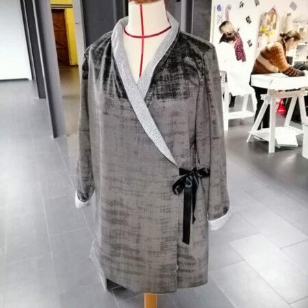 Un manteau noué sur le côté présenté dans l'atelier de Mons